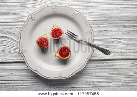 figs raw cutted fig fruits on white plate and wooden table