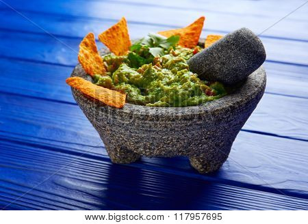 Guacamole with nachos avocado in Mexican molcajete on blue wood table