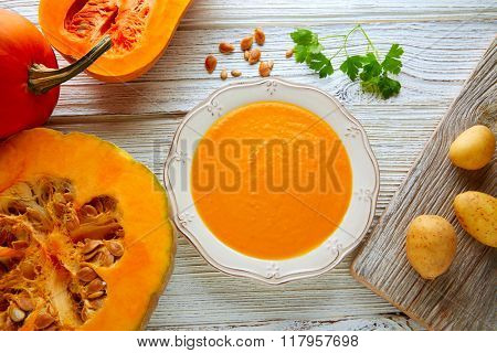 Pumpkin soup cream on a wooden table and ingredients