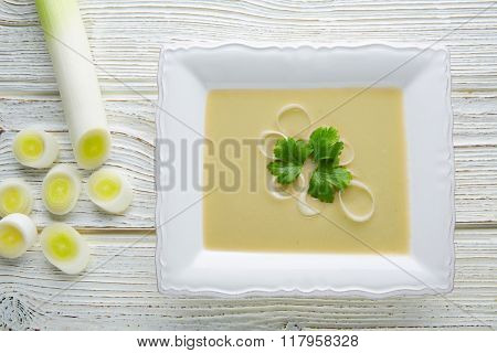 vichyssoise cream soup with leeks on white wood table