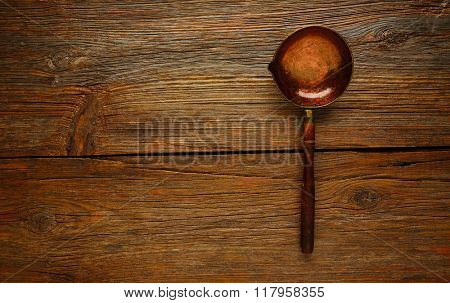 Aged cooper ladle vintage on wooden table retro