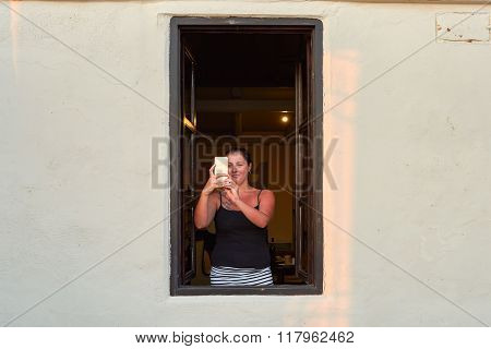 SANTORINI, GREECE - AUGUST 07, 2015: woman take photo of sunset on Santorini island. Santorini, classically Thera, and officially Thira, is an island in the southern Aegean Sea