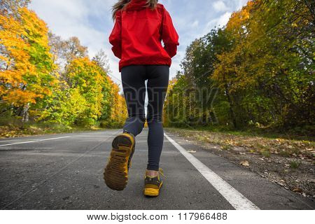 Woman running on the asphalt road in an autumn forest