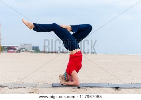 Beautiful young fit woman doing sport exercises, variation of supported headstand posture, salamba s