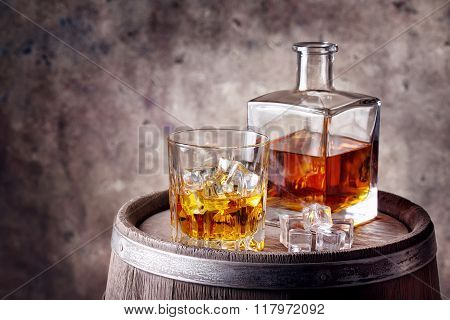 Whiskey with ice on wooden barrel