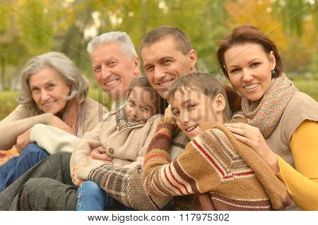Family relaxing in autumn park