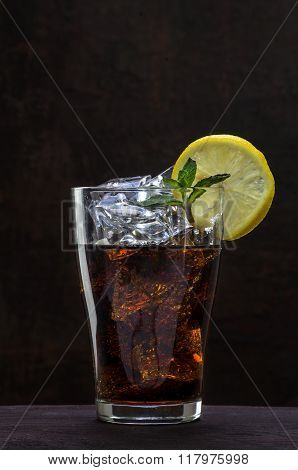 Glass Of Cola With Ice Cubes, Lemon Slice And Peppermint Garnish On A Wooden Table Against A