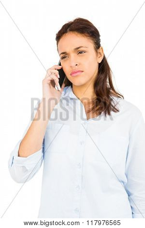 Worried casual woman on phone on white background