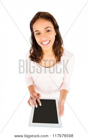 Smiling casual woman using her tablet pc on white background