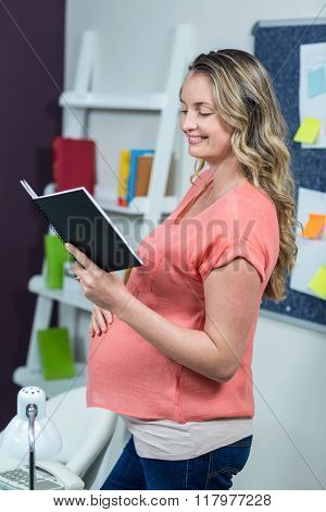 Pregnant woman reading a notebook in an office
