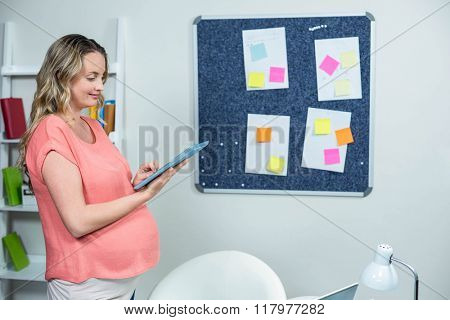 Pregnant woman using tablet in an office