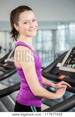 Smiling brunette on treadmill at the gym