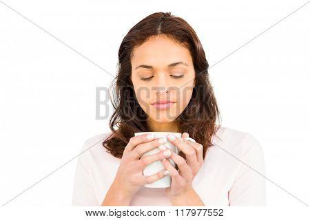 Woman with eyes closed holding mug on white background