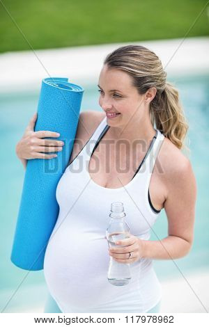 Pregnant woman holding water bottle and mat next to the swimming pool