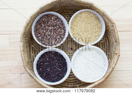 Many types of rice on a wooden table.