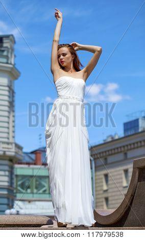 Full length portrait of beautiful model woman with long legs wearing white dress posing summer street