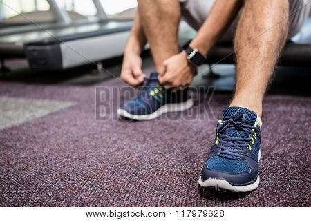 Lower section of man sitting on treadmill and tying the shoelace at the gym