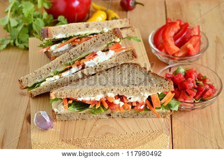 Sandwich with carrots, bell peppers, feta and herbs