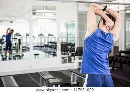 Muscular man doing stretching in the gym