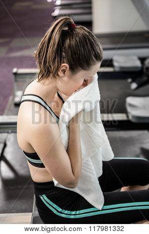 Tired woman on drawing machine wiping sweat at the gym