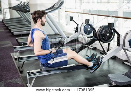 Handsome man doing exercise on drawing machine at the gym