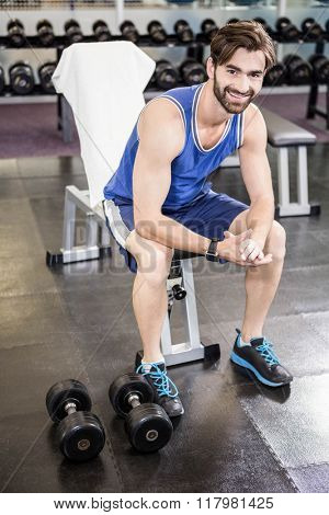 Smiling man sitting on bench at the gym