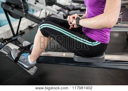 Fit woman on drawing machine looking at smartwatch in the gym