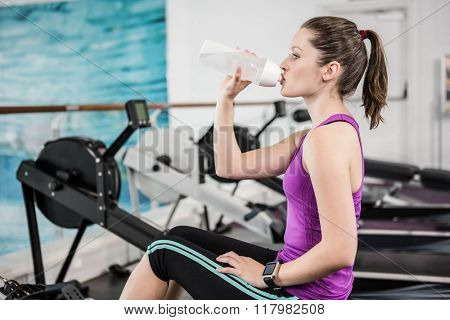 Fit brunette on drawing machine drinking at the gym