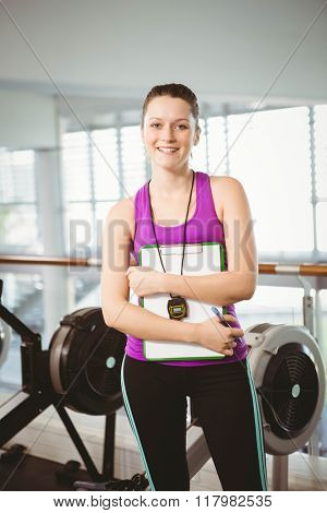 Smiling trainer holding clipboard in the gym