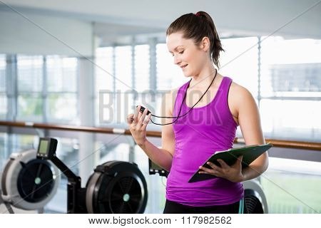 Smiling trainer looking at stopwatch in the gym