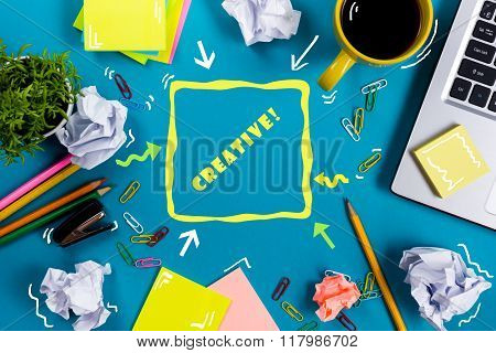 Be creative word. Office table desk with supplies, white blank note pad, cup, pen, pc, crumpled pape