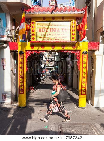 Woman is passing by Buddhist street gate