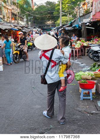 Vietnamese woman in traditional conical hat with baby on hands sells lottery tickets at the wet mark