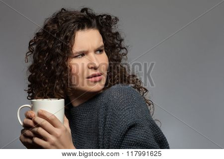 Cheerful young girl with a cup of tea