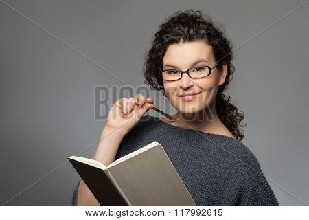 Cute young woman is reading interesting literature