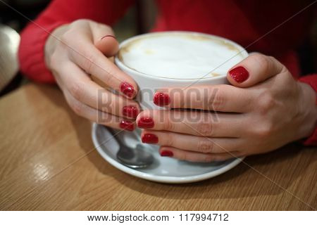 Woman with red nails is holding full cup of coffee.