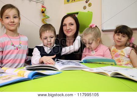 Little boy is hugging his mother and three girls are sitting at the table.
