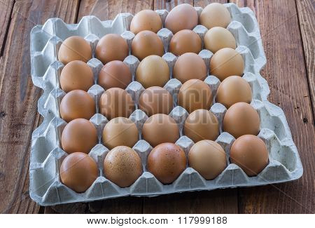 The cardboard egg tray with brown chicken eggs