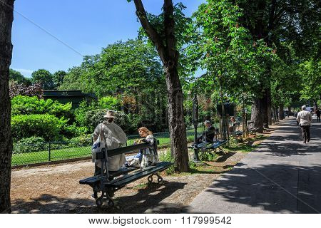 People resting on benches of boulevard under trees shadow