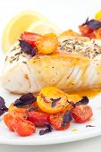 stock photo of halibut  - Pan fried halibut garnished with fennel seeds and spicy mustard sauce served with fried cherry tomatoes salad with purple basil
