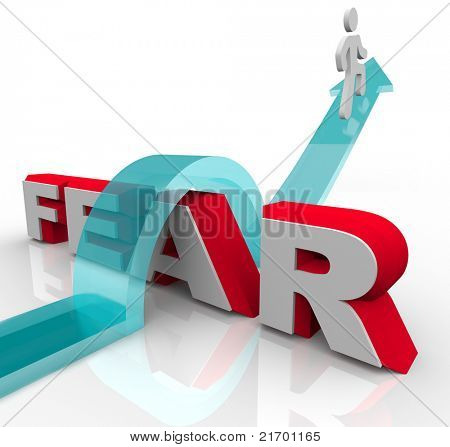 A man jumps over the word fear on an arrow, illustrating the bravery and courage needed to overcome and conquer one's fears and anxieties