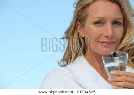 Attractive blonde haired woman with no make up on and drinking a glass of water