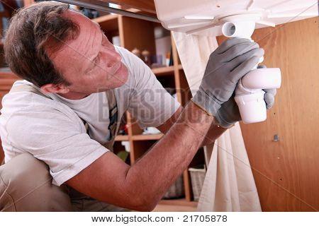 Hombre apropiado de los residuos en el fregadero de la cocina