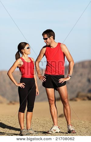 Runner couple in nature taking a break after running in desert mountain landscape.