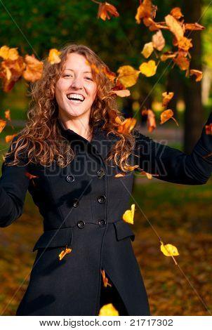 throwing leaves in park