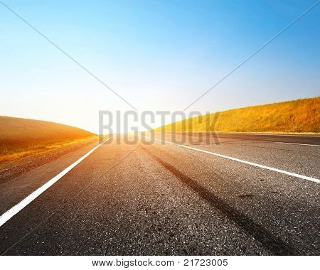 Empty countryside asphalt road and clear blue sky