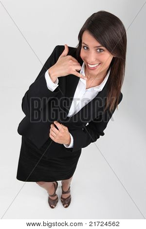 Studio shot of young businesswoman making a telephone sign with hand