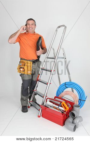 Man on cellphone with ladder and plumbing tools