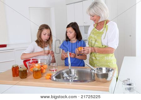 Senior woman making apricot jam with grandkids