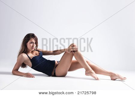 attractive tanned brunette in blue underwear lie on floor, full body shot, small amount of grain added, studio shot